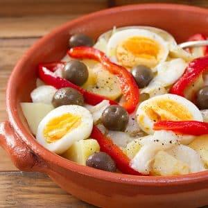 assadeira redonda com lombos de pescada no forno, ovo, batata e pimentos