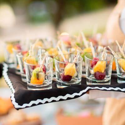 mini copos com fruta em tabuleiro com pano preto