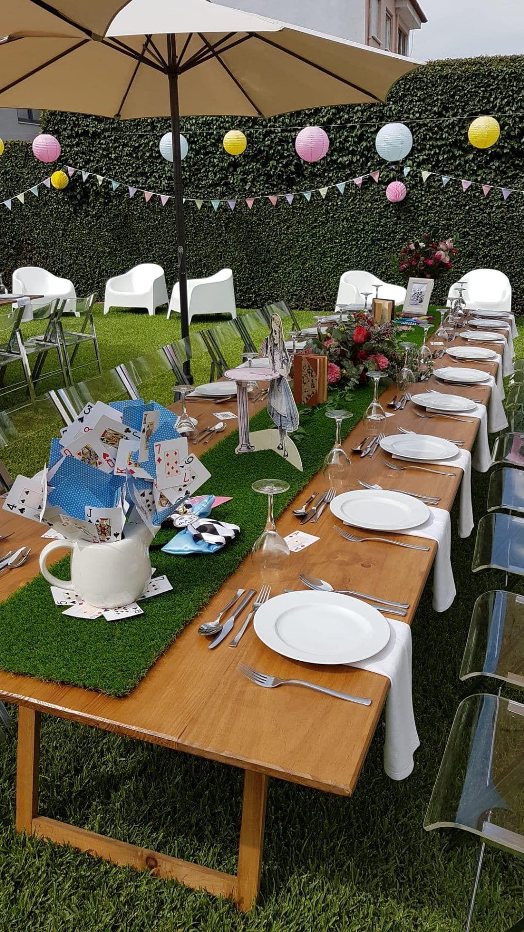 mesa de madeira com pratos e talheres num jardim