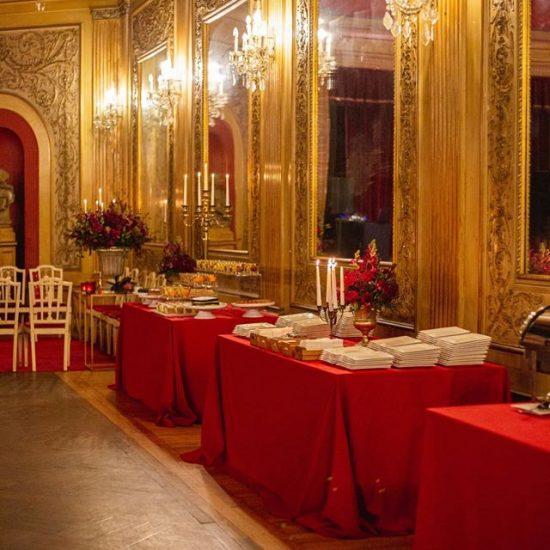 mesas com toalha vermelhas em sala dourada