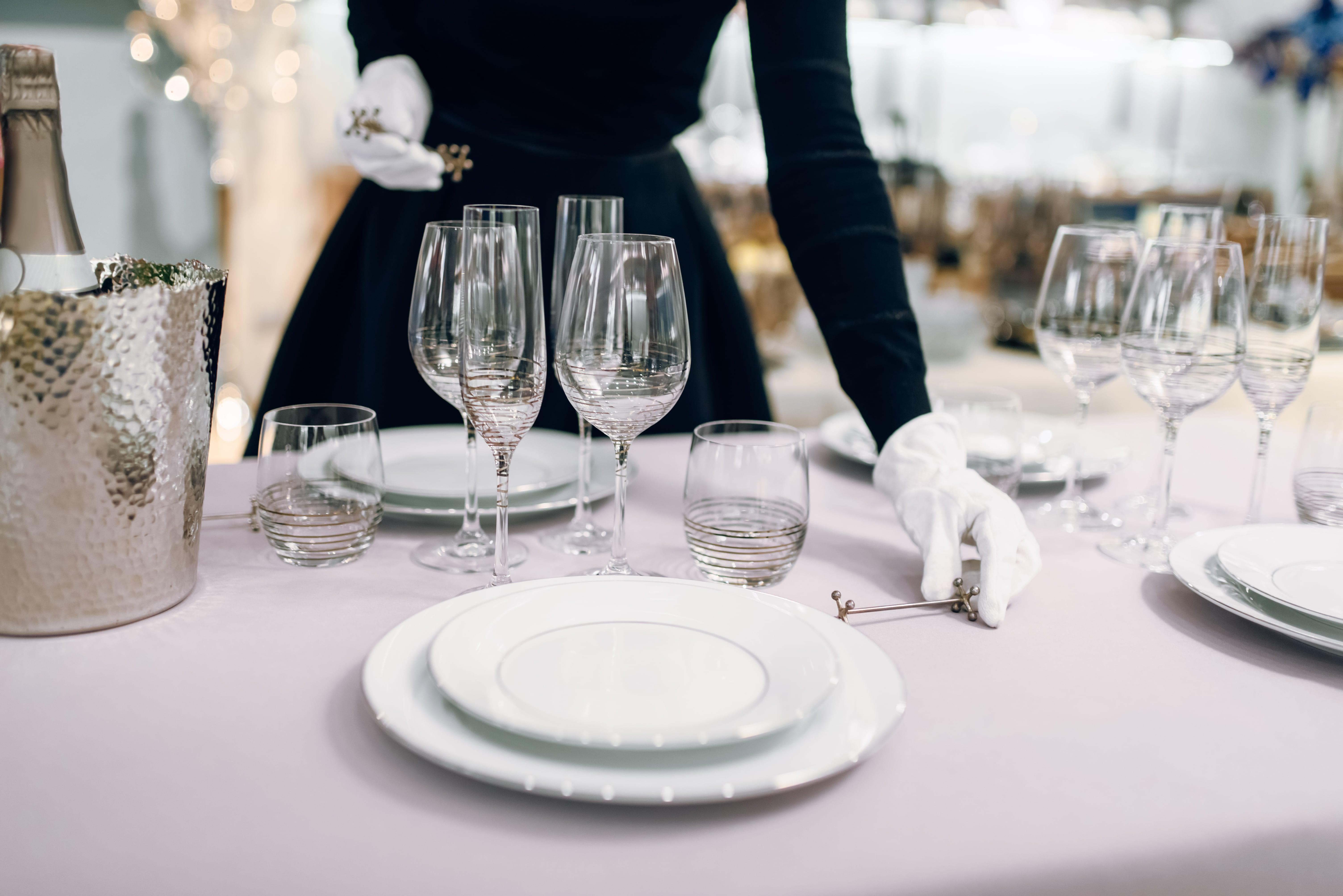 mulher com luvas brancas a por a mesa